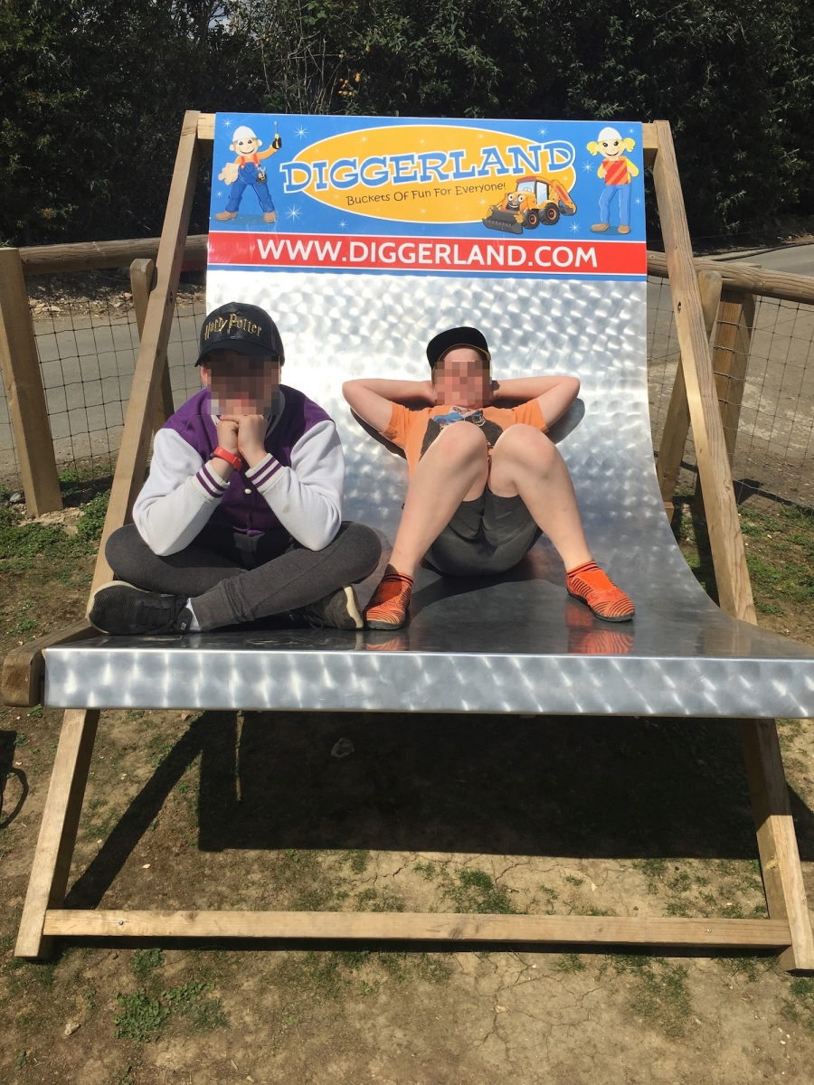 Brother T and R relax on oversized Diggerland-themed deck chair after a long day.