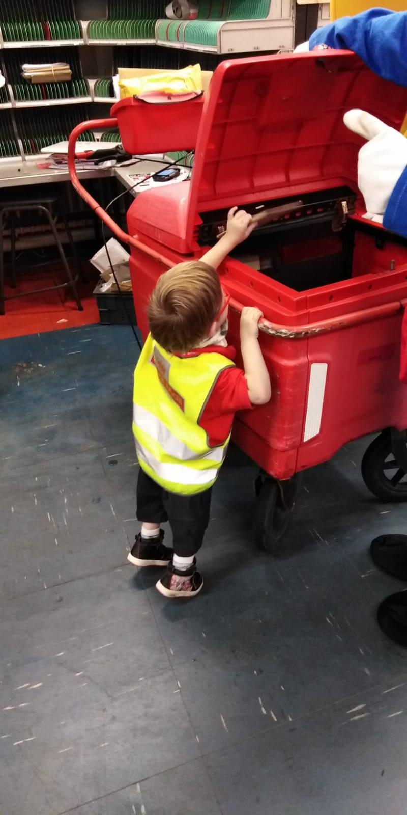 H loads the postal trolley.